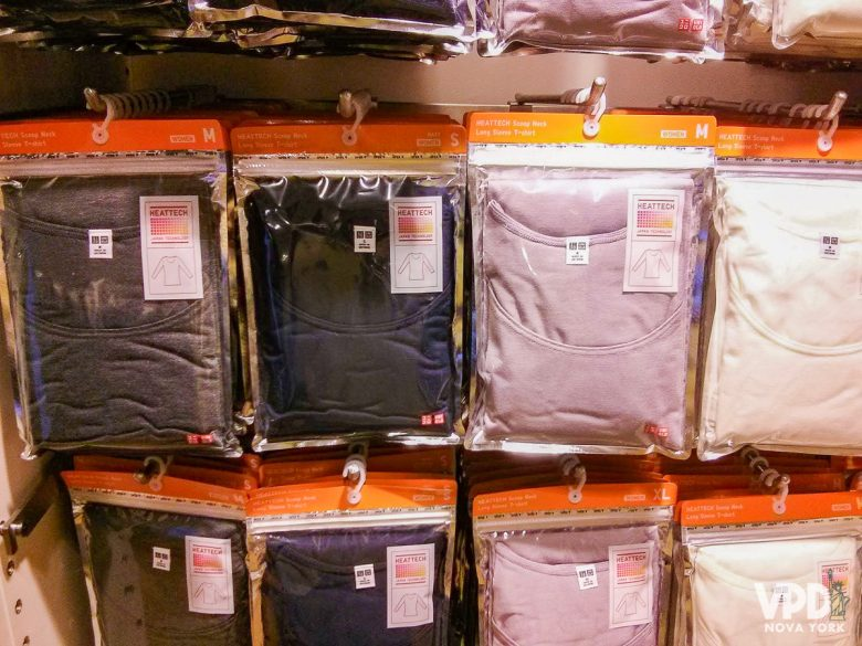 Imagem de várias camisetas térmicas cinzas, azuis, beges e brancas em uma loja. Essas camadas são essenciais pra quem vai encarar o frio de fevereiro em Nova York.