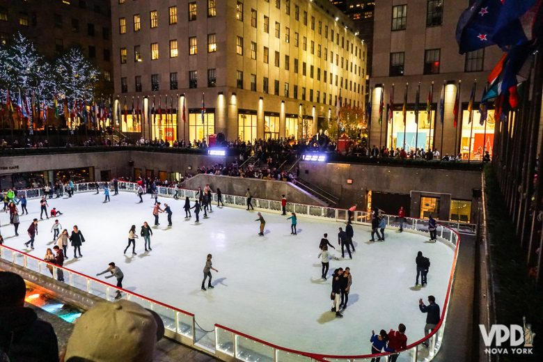 Imagem da pista de patinação do Rockefeller Center em fevereiro. Está de noite e várias pessoas patinam. Os prédios estão iluminados ao redor e muitas pessoas assistem os patinadores.