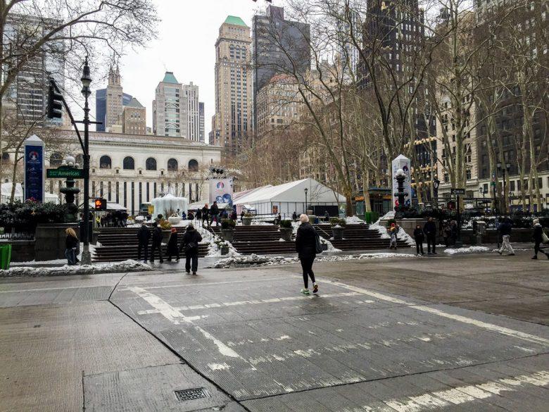 Imagem mostrando o Bryant Park em fevereiro. Ele está mais vazio, e poucas pessoas caminham na calçada. Há prédios ao fundo.
