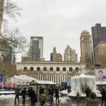 Imagem mostrando o Bryant Park em fevereiro. Ele está mais vazio, e algumas pessoas caminham no parque Há prédios ao fundo e uma fonte congelada.