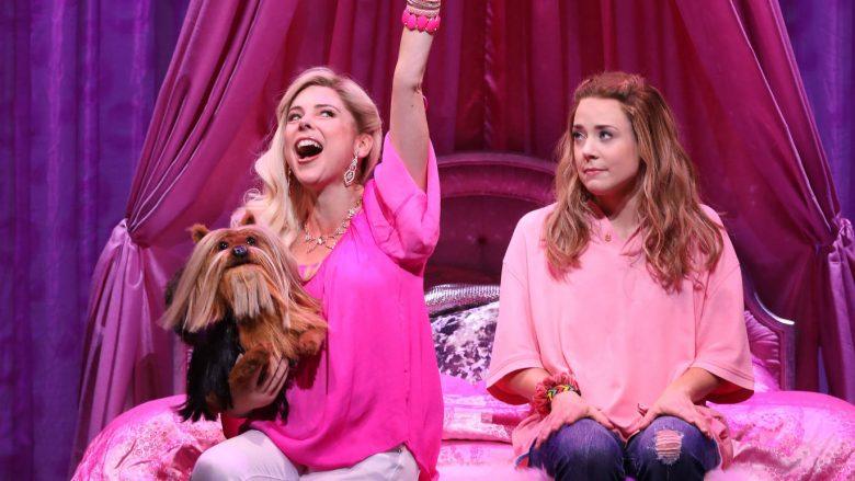 O musical de Meninas Malvadas estreou em 2018 e não voltará para a Broadway. A foto mostra duas das personagens vestidas de rosa, sentadas em uma cama e segurando um cãozinho.
