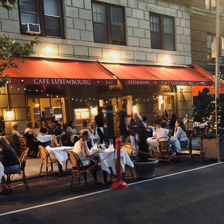 Imagem da fachada do Cafe Luxembourg. As mesas estão espalhadas na calçada e há fios de luzinhas.