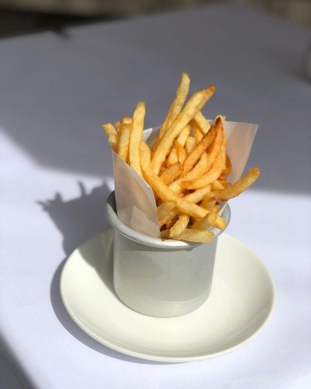 Imagem de uma porção de batatas fritas. Elas estão dentro de um potinho branco que está apoiado em um pratinho branco e em uma mesa branca.