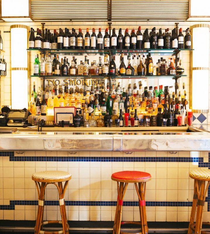 Imagem do bar do Cafe Luxembourg. Há várias garrafas de bebidas em 3 prateleiras, em frente a uma parede espelhada. 3 banquinhos com assentos coloridos estão em frente ao bar.