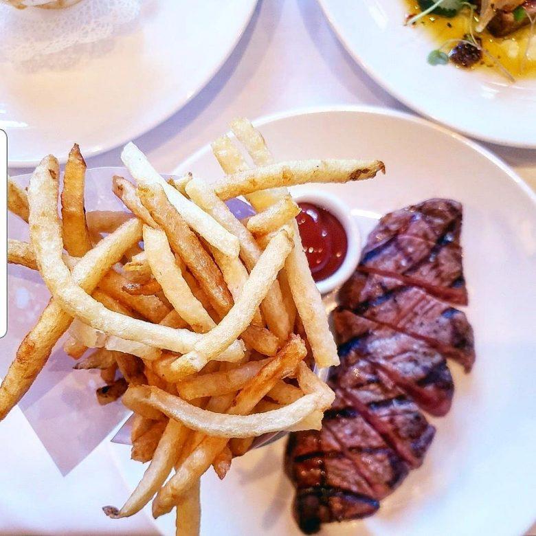 Imagem de uma porção de batatas fritas, um potinho com ketchup e um filé de carne vermelha em um prato branco. O steak frites é um dos pratos do Cafe Luxembourg.