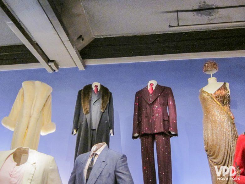 Figurinos do filme Chicago: um casaco branco de pele, um terno preto, um terno vermelho brilhante e um vestido dourado, todos vestidos em manequins.