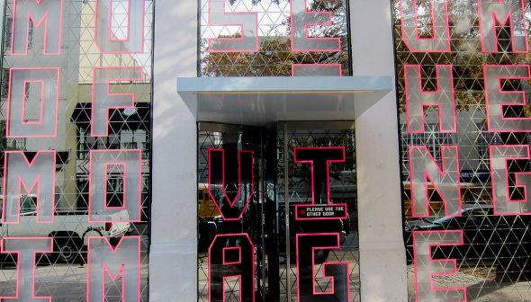 Foto da entrada do Museum of Moving Image, com letras em vermelho em uma estrutura espelhada.