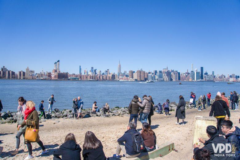 Imagem de Nova York em março. Várias pessoas estão sentadas nas margens do rio, e o Skyline da cidade está ao fundo.