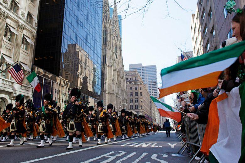 Imagem de uma parada de St Patrick's Day que acontece em março. Algumas pessoas marcham na rua e outras assistem segurando bandeiras da Irlanda nas laterais.