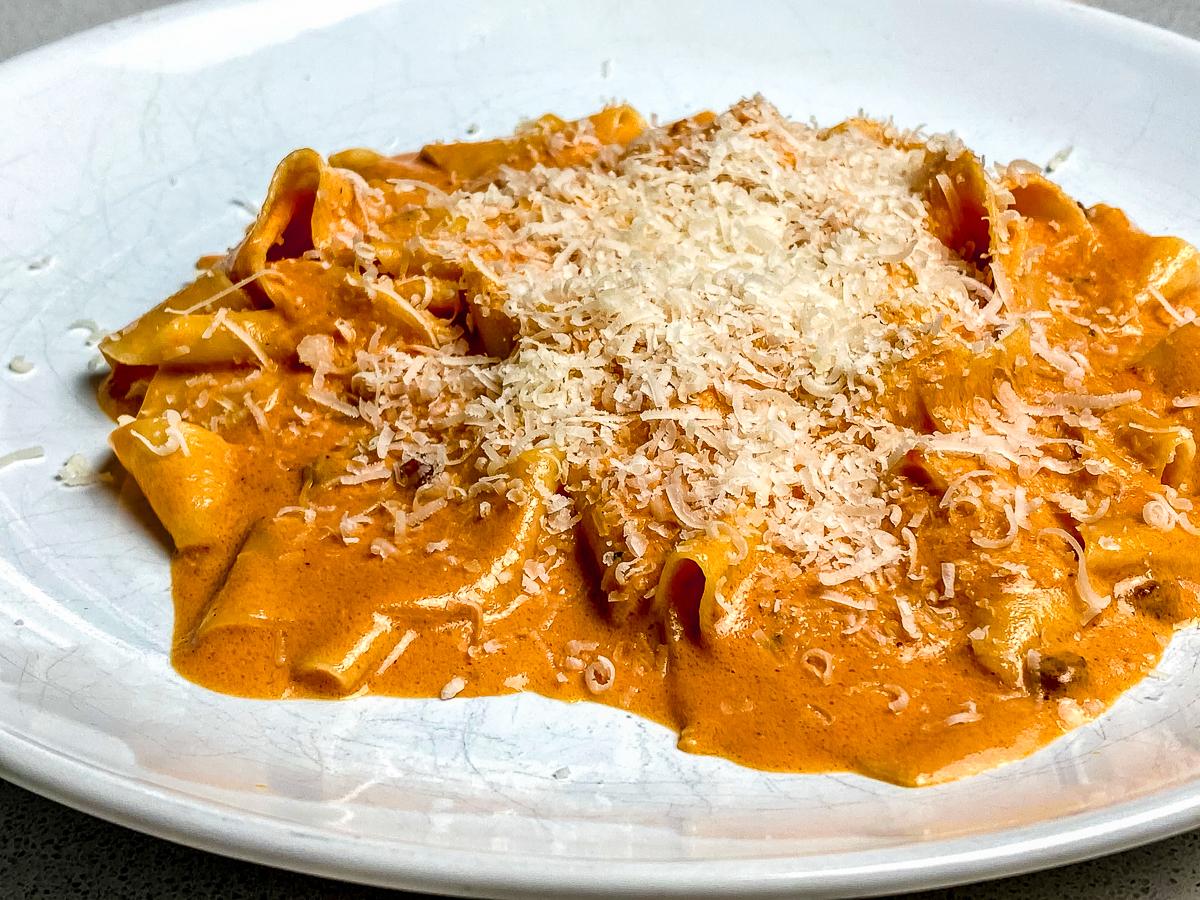 Imagem de um prato branco com uma porção de macarrão com molho vermelho com queijo parmesão em cima.