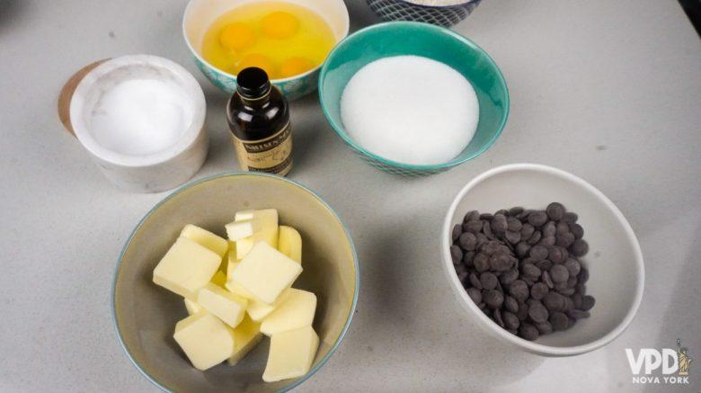 Foto com os ingredientes do brownie. Há potinhos com ovos, sal, açúcar, manteiga, baunilha e gotas de chocolate.
